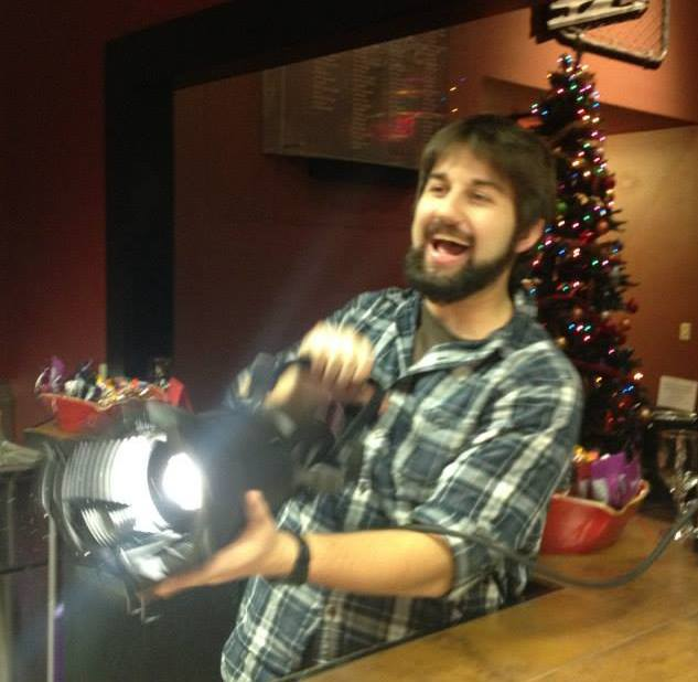 """Picture of the author behind the service desk a in a concession stand at the theater. The background has a large christmas tree and two candy bowls on the counter. In the authors hands he is holding a large and bright spotlight pointing it towards the camera with a large grin on his face.  He is wearing a plaid shirt. The caption reads: """"A younger me color rendering some things with a Source4 Jr. I still have the shirt. Wow"""""""
