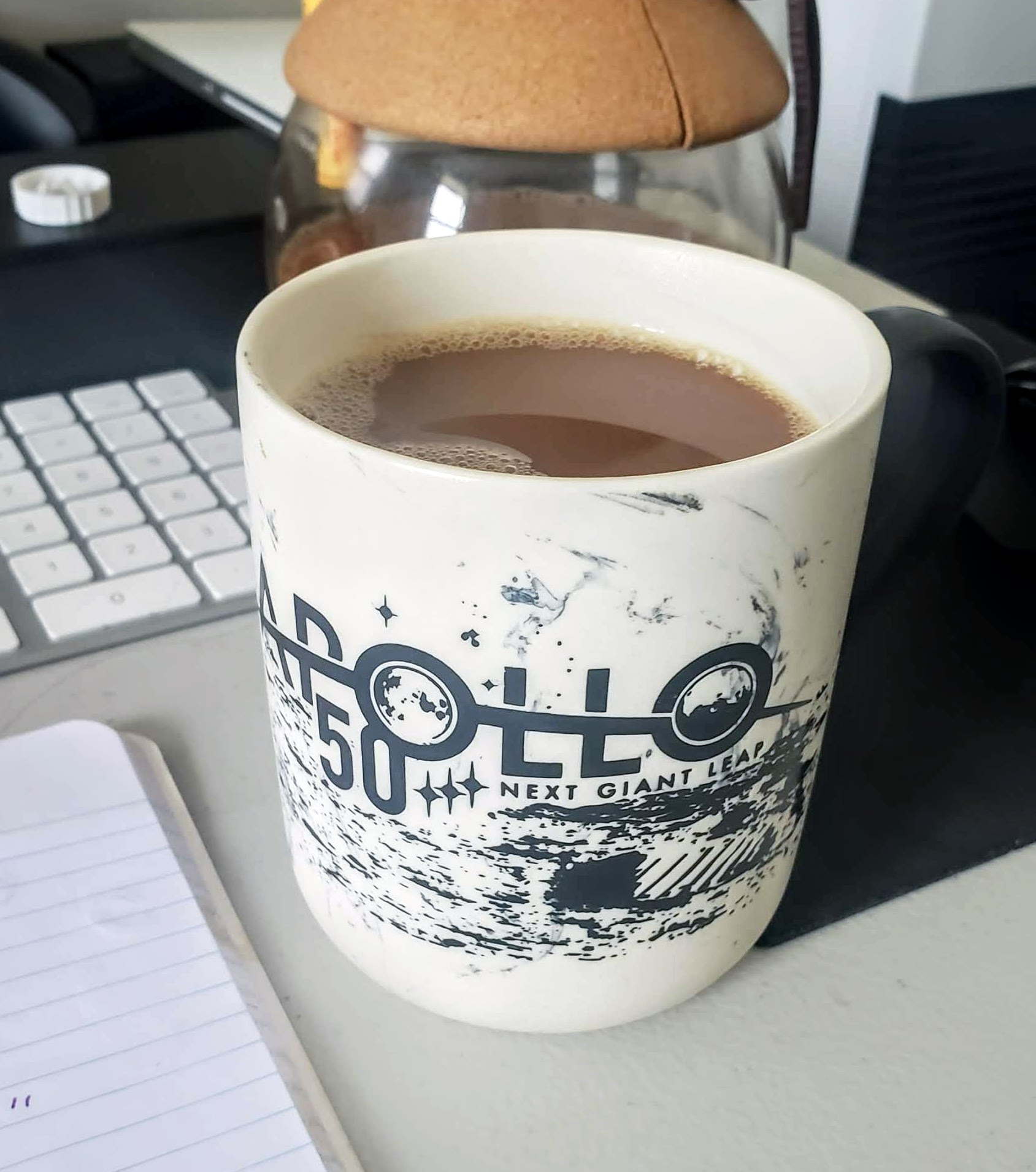 "Cup of coffee with cream, the color is a light brown. In a cup labeled ""Apollo 50th Anniversary."" Sitting on the author's home desk. Keyboard and coffee pot visible in the background."
